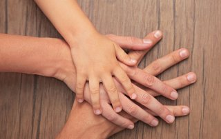 Family hands on wooden background